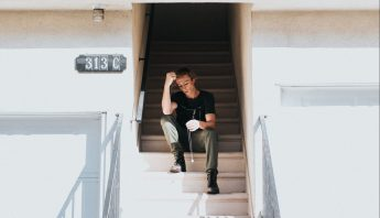 A teenage boy sits on some stairs in thought.